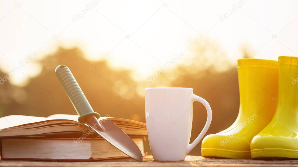 Coffee and gardening concept : Cup of coffee, book, and garden equipment on wooden table with sunlight in morning time