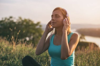Beautiful sporty woman with headphones enjoys listening music while sitting on exercise mat  with a cityscape and river behinde her.Image is intentionally toned.