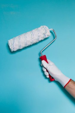 Image of man holding paint roller in front of blue wall.