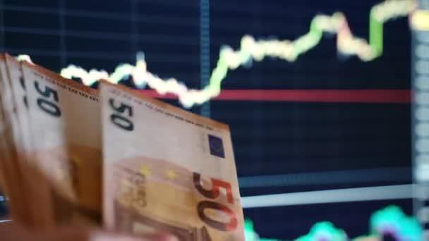 Weltbörsen stürzen ab, Papierwährungen verlieren an Wert, Menschen zählen Euroscheine und werfen sie vor dem Hintergrund von Auf- und Abwärtstrenddiagrammen nach unten. Finanzkrise und Wirtschaftskrise