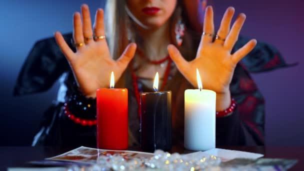 Černý rituální výkon v tmavé místnosti se svíčkami a lidskými fotografiemi, generická čarodějnice zvedající ruce nahoru a dolů nad červené, černé a bílé svíčky a hláskovací lektvar. Strašidelný rituál, smrt a peklo