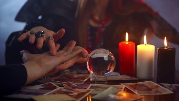 Mladý věštec, který čte čáry štěstí na mužské dlani nebo ruce, mystický esoterický nebo paranormální chiromantický koncept. Budoucí předpověď s křišťálovou koulí a hořícími svíčkami v temné místnosti. Symbolismus
