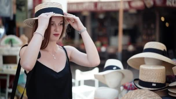 Hezká holka zkouší letní panamský klobouk a dívá se do zrcadla. Stylové ženské doplňky, letní ochrana před sluncem. Atraktivní dáma kráčí na bleším trhu a hledá elegantní hlavu