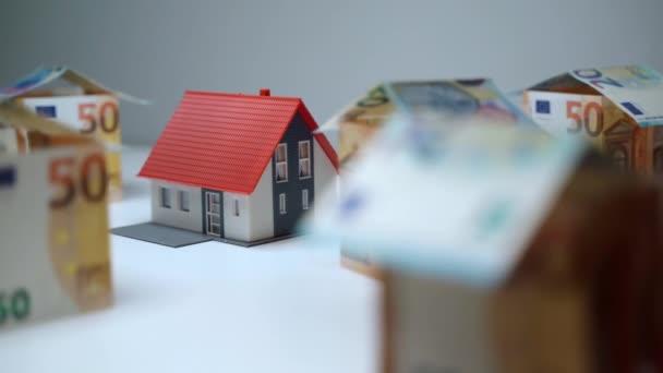 Investitionen in Immobilien, Geld verdienen und sparen für den Kauf eines neuen Wohnhauses. Häusermodell aus Plastik, umgeben von Euro-Banknoten, Person, die kleine Häuserminiaturen mit Papiergeld konstruiert. Real