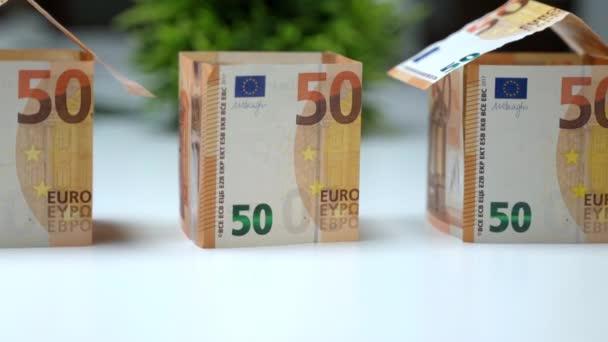 Tři malé bytové modely z eurobankovek, mansardový rám s papírovou střechou. Papírové měnové investice do nemovitostí, finanční transakce se stavebním průmyslem