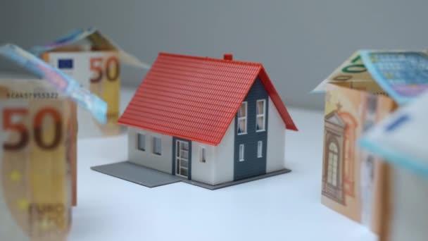 Sparen Sie Geld für den Kauf von Immobilien, Finanzinvestitionen in Wohnprojekte. Kleines Plastikhaus mit rotem Dach, umgeben von Miniaturhäusern aus Euro-Scheinen. Immobilienkredite