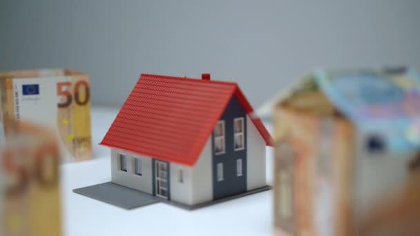 Immobilieninvestitionskonzept, Ersparnis beim Kauf eines neuen Wohnhauses und beim Umzug. Plastikhaus-Miniatur umgeben von Euro-Banknoten, Person konstruiert kleines Hausmodell mit Papierwährung