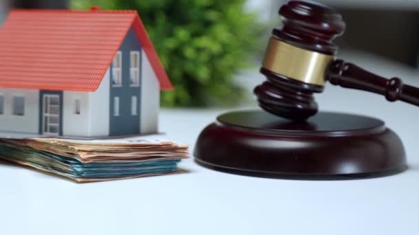 Miniaturní plastový dům ubytovaný na hromadě peněz v blízkosti dřevěné soudcovské kladívko, koncept aukce nemovitostí. Finanční transakce, investice a výdaje při nákupu nebo prodeji domu