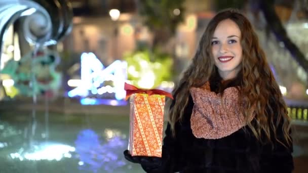 Portrait of amazing smiling woman on glowing fountain background, happy female with curly hair and red lips holding christmas gift and looking on camera. Unforgettable christmas mood in the air