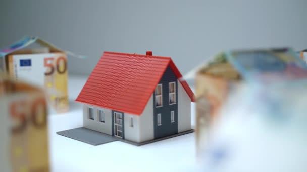 Šetřit peníze na nákup nemovitostí, velké finanční investice do budoucího majetku. Detailní záběr domu makléřství a euro papírové měny, realitní spolupráce a pronájem podnikání
