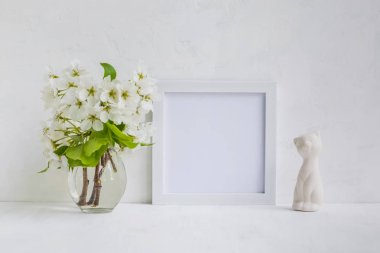 Mockup with a white frame and white flowers in a vase on a light background