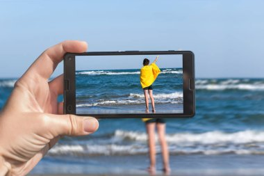 Female taking a picture of a boy on the beach on the phone. Happy teen boy having fun on the sand n the beach.Travel and family concept