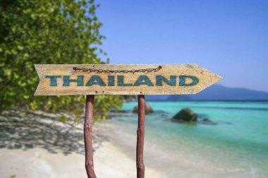 Thailand wooden arrow road sign against beach background. Travel to Thailand concept.