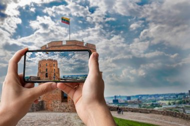Tourist taking photo of Gedeminas tower in Vilnius city center, Lithuania