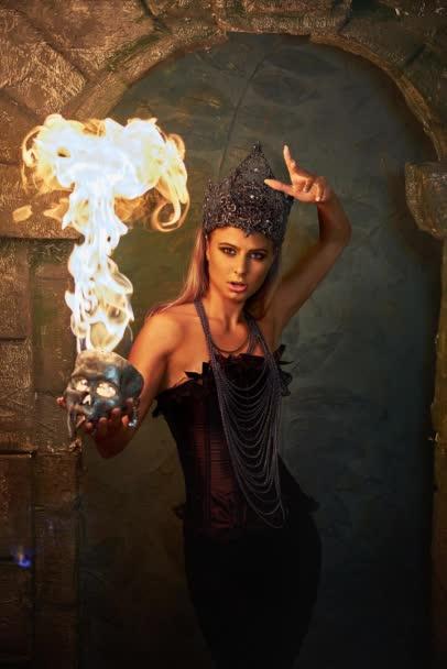 Mädchen in gotischen Tracht hält einen brennenden Schädel in Rauch