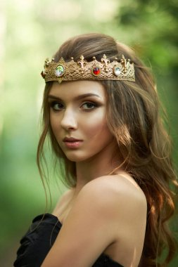 young, beautiful girl in a black dress with a crown in the forest