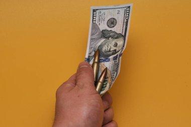 Dolar banknotları ve sarı arka planda mermiler tutan kişinin kırpılmış görüntüsü.
