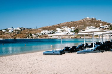 tropical beach chairs with umbrella at the beach of Mykonos Greece
