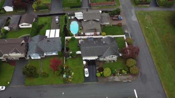 Letět přes bohaté domy v Kanadě se zelenou trávou a bazénem