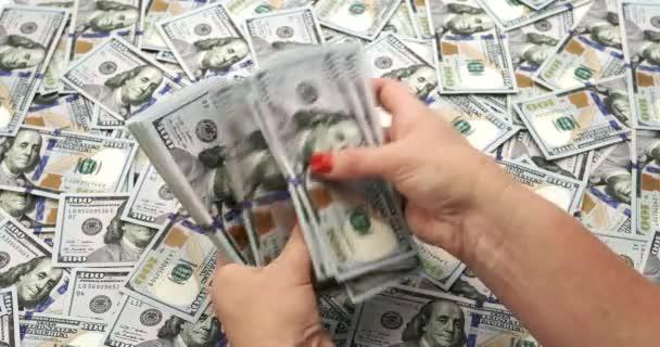 Počítání dolarů na pozadí stodolarových bankovek