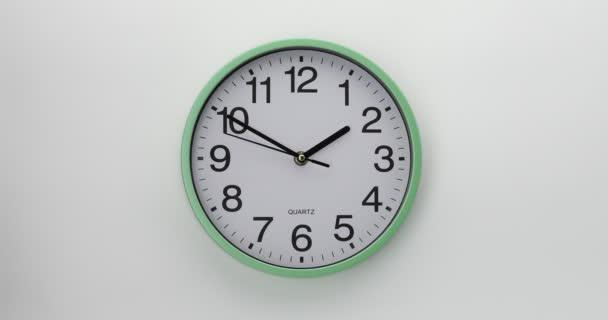 Křemenné nástěnné hodiny na bílém pozadí. Hodiny ukazují deset minut do dvou. Video DCI 4K.