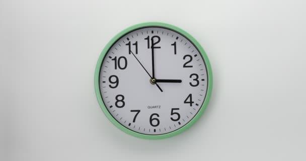 Křemenné nástěnné hodiny na bílém pozadí. Hodiny ukazují tři hodiny. Video DCI 4K.