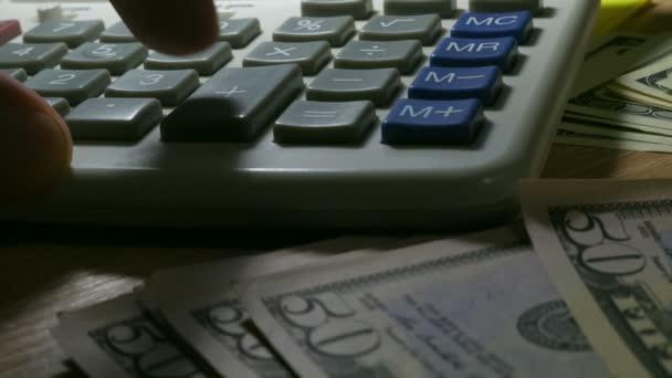 Muž, pomocí kalkulačky pro obchodní výpočty. Detailní záběr z ruky, peněz a kalkulačka
