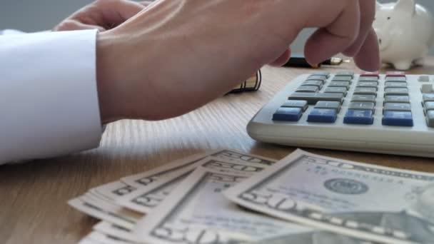 Mann mit Taschenrechner für die Budgetierung. Vermögens- und Sparkonzept.