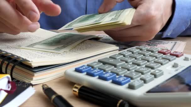 Muž s Kalkulačka a knihy počítání dolarové bankovky.
