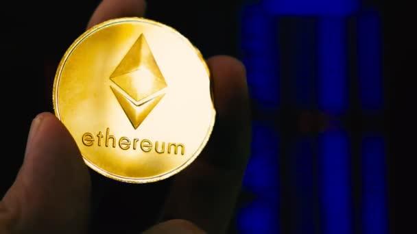 Kezében Ethereum Eth érme és a tőzsde adatok. Cryptocurrency.