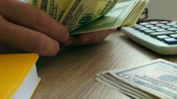 Detailní záběr z rukou, že počítání dolarové bankovky. Peníze na stůl. Rozpočtové koncepce