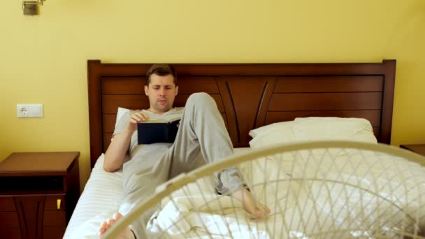 A man is reading a book lying in bed. Summer heat. The fan works.