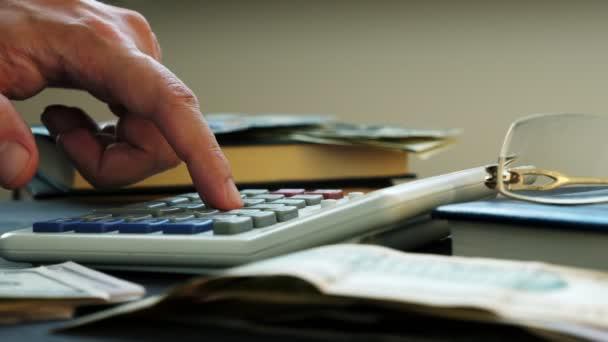 Ruční počítání na kalkulačce a peníze na stůl