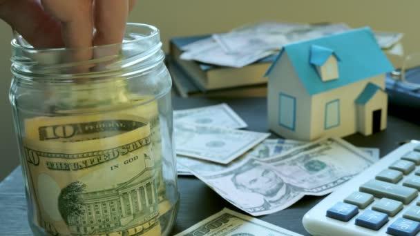 Hände, Geld in das Glas und Modell des Hauses. Einsparungen für den Kauf von Immobilien oder Hypotheken.