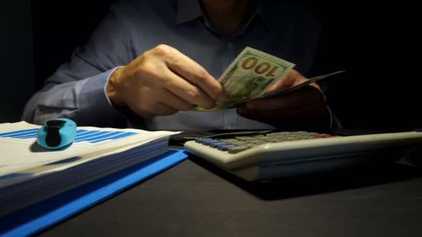 Člověk je počítání dolarové bankovky a použití kalkulačky. Půjčky v kanceláři