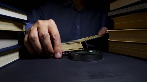 Man using magnifying glass for reading the book. Investigation and developing.