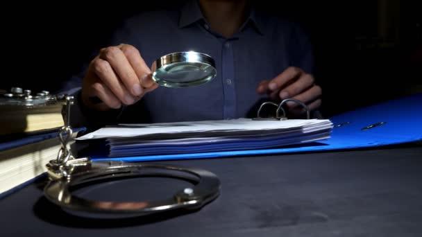 Muž, použití lupy pro kontrolu obchodních dokumentů pro vyšetřování. Daňové úniky