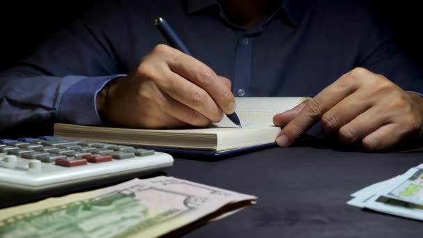 Accountant writing in the accounting book financial figures. Business calculation and home finances.