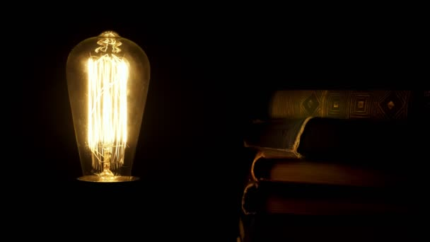 Old styled retro bulb flickering near pile of vintage books.