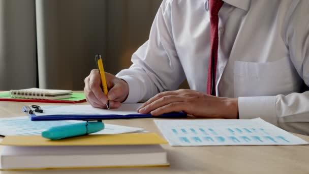 Detailní záběr manažera, který pracuje s grafy a papíry. Papírování v kanceláři.