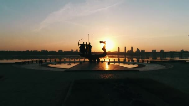 Monument to the founders of Kyiv at sunrise, beautiful cityscape in fiery sunlight. Statue of Kyi, Shchek, Horyv and Lybid over the Paton bridge. Capital of Ukraine