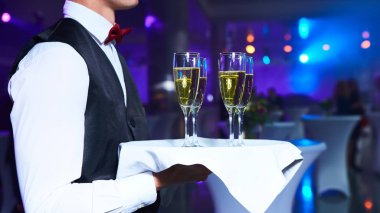 Waiter serving champagne on a tray at party.