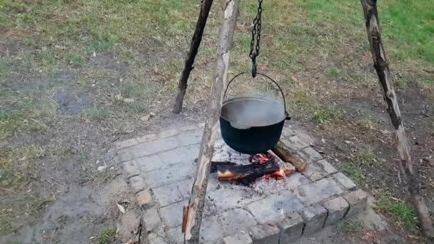 Öntöttvas üstben főz a szabadban. Tűzön sütni. Étel egy üstben a tűzön. Főzés élelmiszer a természetben az üstön.
