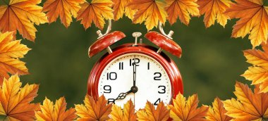 Daylight savings time, autumn concept - red alarm clock with orange leaves border - web banner idea