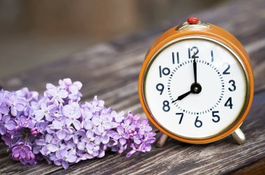 Daylight savings, spring forward concept - orange alarm clock and purple lilac flowers