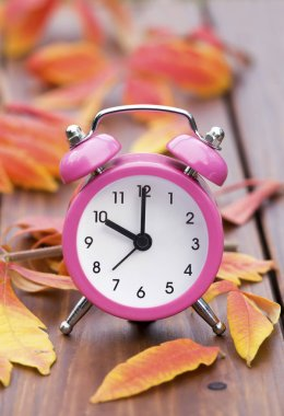 Daylight savings time - alarm clock with autumn leaves