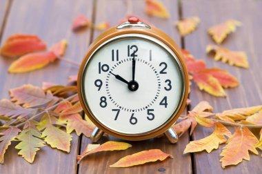 Daylight savings time - orange retro alarm clock with autumn lea