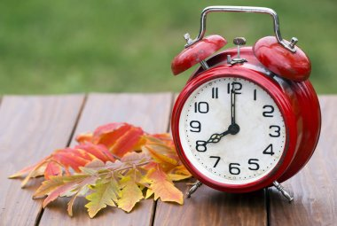 Clock with orange autumn leaves, daylight savings time concept