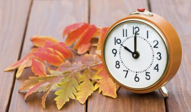 Daylight savings time, alarm clock on a wooden background