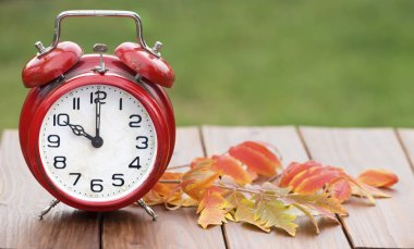 Daylight savings time, retro alarm clock on a wooden background,